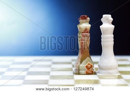 Pair of chess Kings made from Onyx on board against dark background