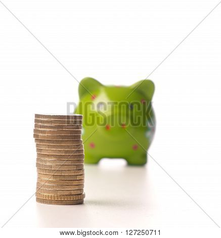 Pile of Euro coins in front of a green piggy bank selective focus on foreground
