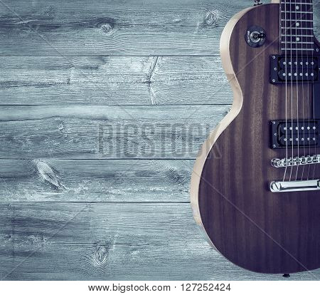 Part of the orange electric guitar on wooden background. A place for writing of the text
