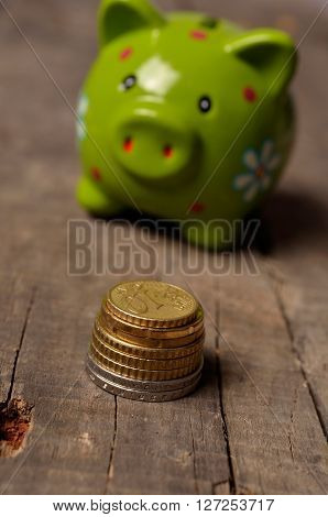 Pile of Euro coins in front of a green piggy bank