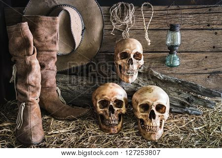still life three human skull on hay with traditional leather boots and american west rodeo brown felt cowboy hat background vintage and dark tone for horror halloween
