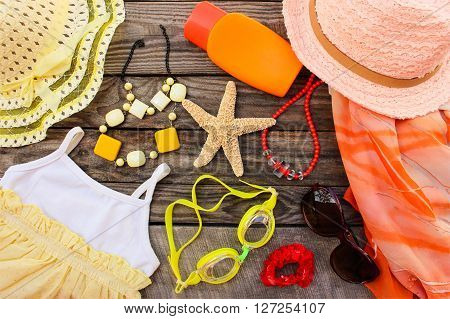 Summer women's clothing and beach accessories for your sea holiday on old wooden background. Toned image.