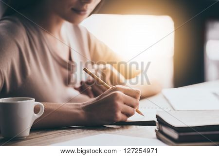 Making some notes. Close-up part of young woman writing in notebook while sitting at her working place