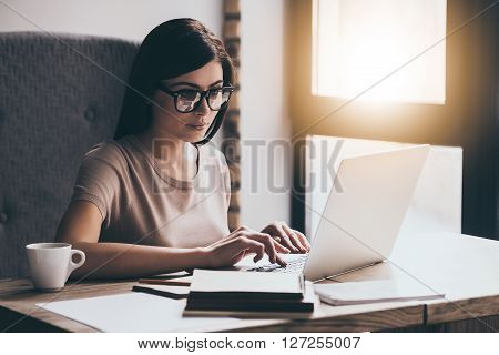 Concentrated at work. Young beautiful woman using her laptop while sitting in chair at her working place
