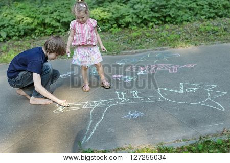 Sibling children are sharing sidewalk chalks and drawing on asphalt surface