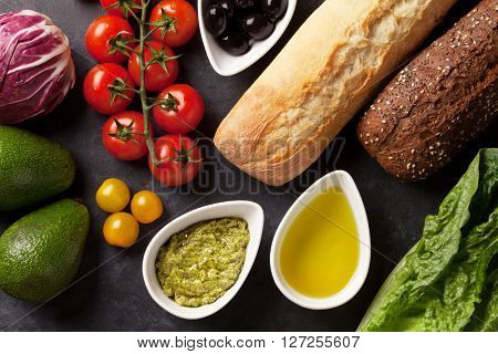 Vegetarian ciabatta sandwich cooking with romaine salad, avocado, olives and tomato cherry over stone background. Top view