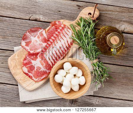 Prosciutto and mozzarella on wooden table. Top view