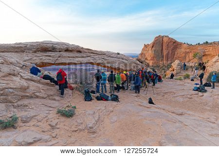 UTAH USA - APRIL 25 2014: people are waiting for a sunrise at Mesa Arch in Canyonlands National Park