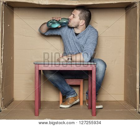 Homeless Man Drinking Alcohol From A Bottle