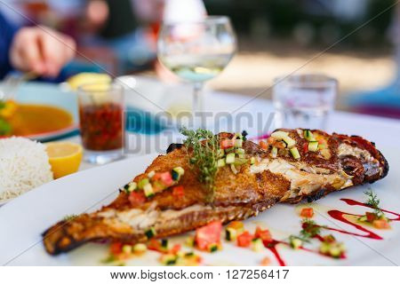 Close up of delicious grilled fish served for lunch with white wine