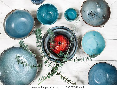Many turquoise clay empty plates and red decorative ceramic pomegranate on white wooden background. Flat lay on set of trendy empty plates and food decor. Organic food, pottery, decoration concept