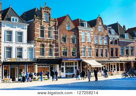 Delft, Netherlands - April 8, 2016: Colorful street view with traditional dutch houses on the square, cheese shop, bicycles, people walking