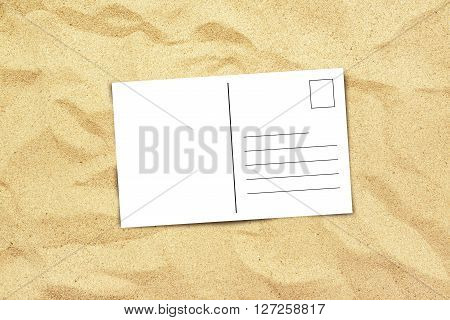 Blank postcard on beach sand top view of copy space for summer holiday vacation message in a letter