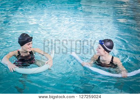 Smiling women in the pool with foam rollers at the leisure center