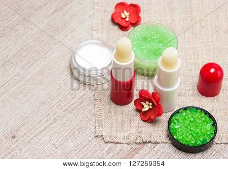 Cosmetics for lip skin care: sea salt, natural honey scrub with essential oils, lip balms and cream with flowers on shabby wooden surface and sackcloth napkin. Copy space