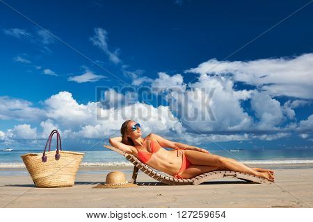 Woman in bikini lying on tropical beach at Seychelles