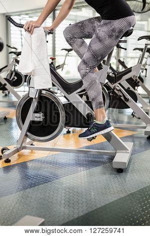 Lower section of fit woman on exercise bike at the gym
