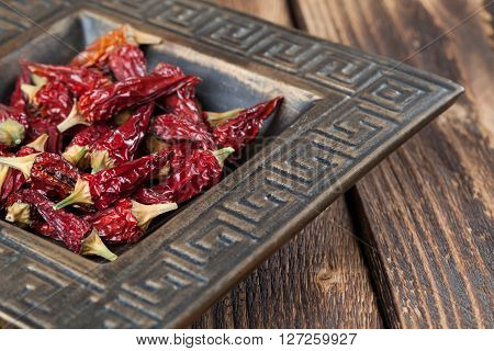 Dried red chili peppers in a bowl. Shallow dof