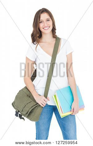 Portrait of happy female college student holding books and shoulder bag while standing on white background
