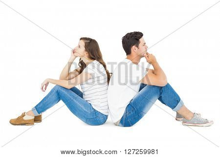 Thoughtful couple sitting on floor back to back on white background