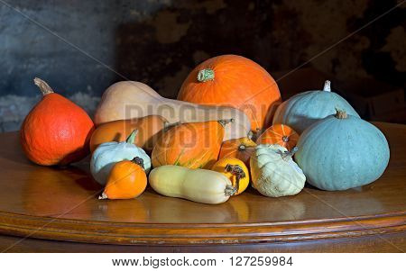 a few squashes pattypanes melones and courgettes on the old cherry desk with dark background