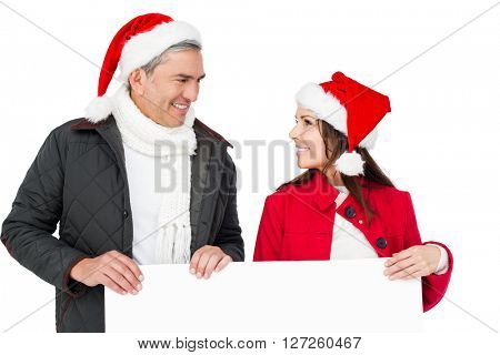 Festive couple with santa hat holding a white poster on white screen
