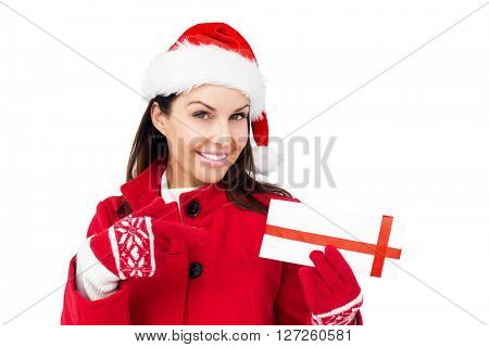 Beautiful brunette pointing a christmas gift on white background