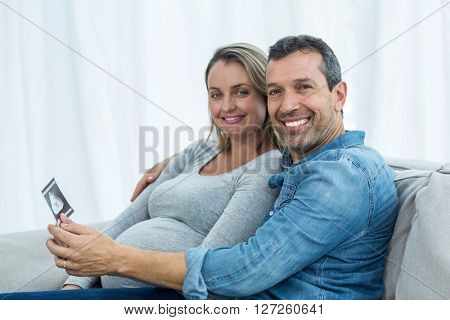 Portrait of couple sitting on sofa and looking at ultrasound scan