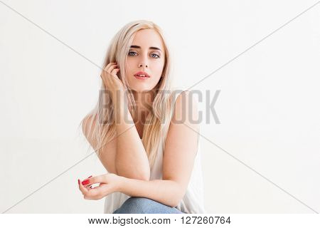 Successful confident woman with nude makeup on white background. Blonde student girl isolated on white. Fashion portrait of young girl in light studio.  Confidence, purity, woman success concept.