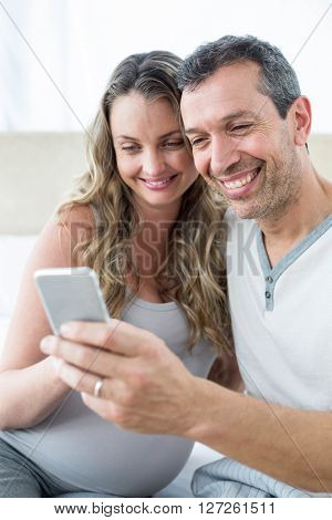 Couple looking at smartphone in bedroom