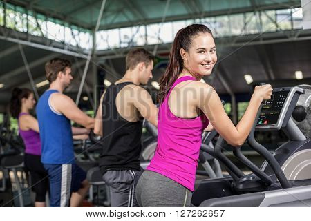 Fit people on elliptical bike at gym