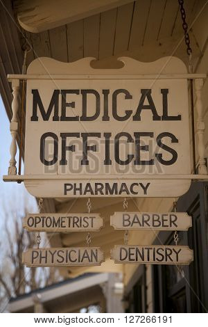 An old, wooden, medical offices sign at the ghost town of Laws in California