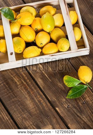 Wooden crate full of fresh lemons on a rustic wooden background. Free space for text .
