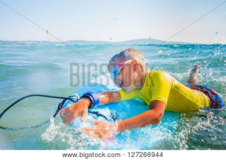 Little boy with surf board having fun in sea against sea ** Note: Soft Focus at 100%, best at smaller sizes