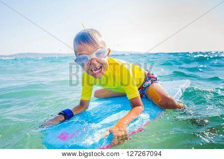 Little boy with surf board having fun in sea against sea