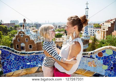 Smiling Mother And Baby Having Fun Time At Park Guell, Barcelona