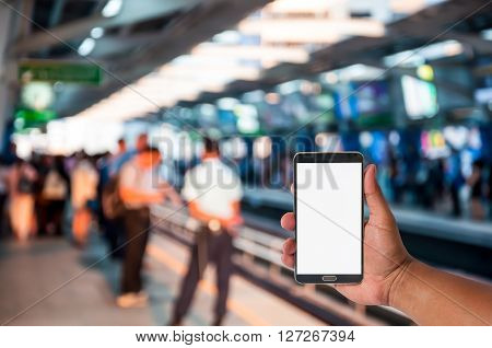 hand of man hold mobile phone over blurred of people waiting at sky train platform