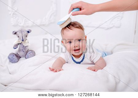 A cute little baby is looking into the camera on the white wall whith blue eyes with bear. Mother combs baby.