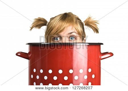 Horizontal portrait of a young blonde woman's head coming out of a red cooking pot isolated on white background