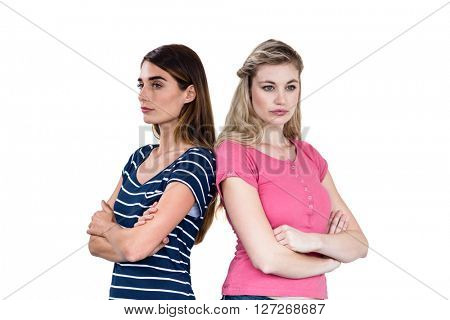 Upset friends with arms crossed while standing over white background