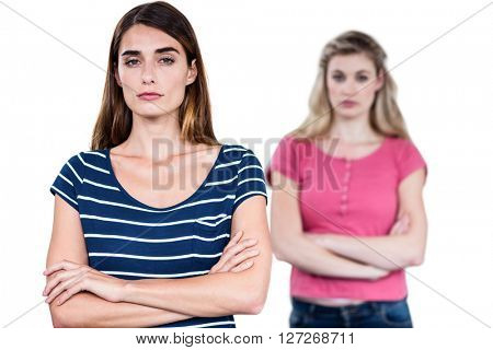 Portrait of upset friends with arms crossed while standing over white background