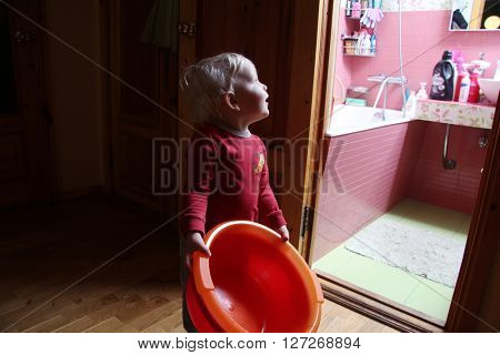 Little boy holding a plastic basin at home