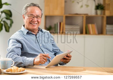 Cheerful mature Vietnamese man using digital tablet