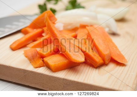 chopped carrot chopped onion on a chopping Board and a knife