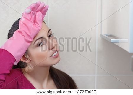 Tired beautiful caucasian woman in protective gloves after cleaning. Tired female after housework