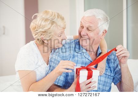 Happy senior couple opening gift in bedroom at home