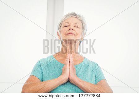 Senior woman with eyes closed praying at home