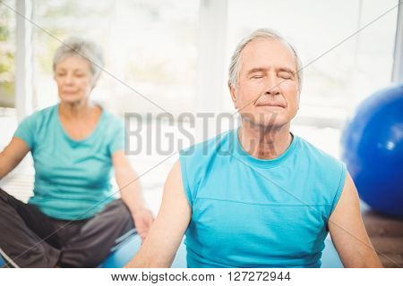 Senior couple meditating with eyes closed at home