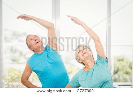 Senior couple with arms raised while exercising at home