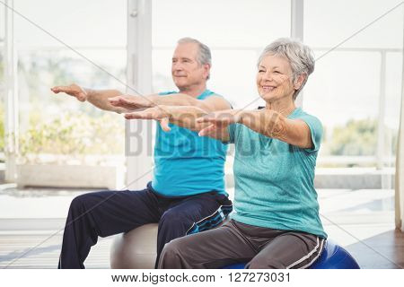 Happy senior couple performing exercise while sitting on exercise ball at home